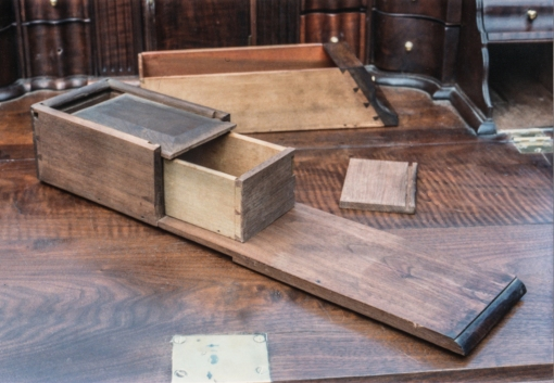 When the lower drawers at the sides of the interior are pulled out, a spring lock, accessed from the upper long drawer of the case, is sprung to allow a section of the ledge under the drawers to be pulled out reveling a hidden drawer.